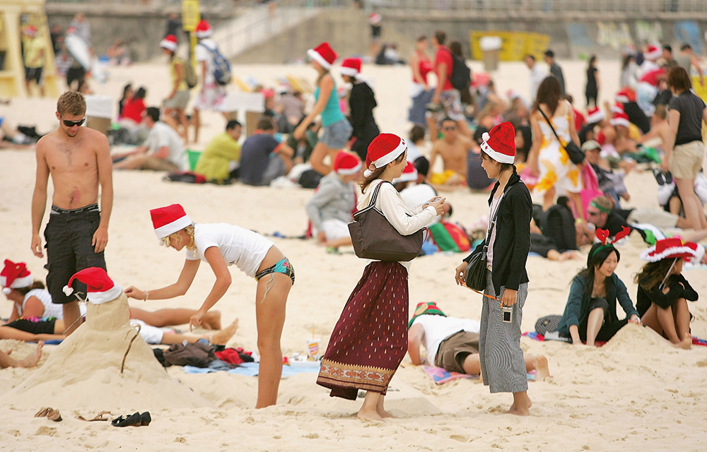 "SYDNEY, AUSTRALIA - DECEMBER 25: A young woman wearing a Santa hat works on a ""snowman"" made out of sand on Bondi Beach on December 25, 2007 in Sydney, Australia. Bondi Beach is a popular destination for tourists on Christmas Day. (Photo by Ezra Shaw/Getty Images)"